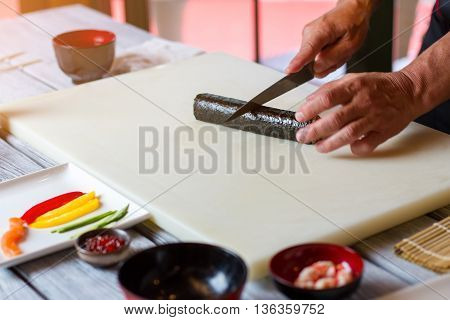 Hand with knife cuts sushi. Long sushi roll. Japanese chef cooks futomaki rolls. Kitchen table in sushi restaurant.