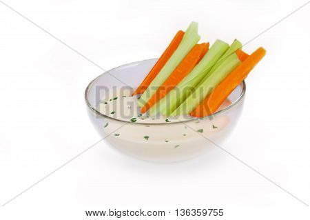 Celery and Carrot sticks in bowl of dip cut out on white background