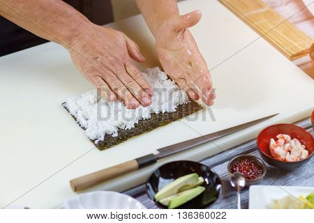 Hands touching white rice. Nori leaf beside a knife. Boiled rice for uramaki rolls. Sushi chef working in kitchen.