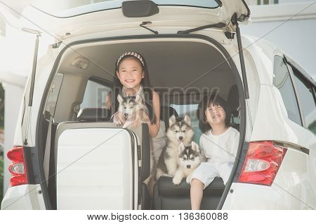 Happy asian children and siberian husky puppรำห sitting in the car