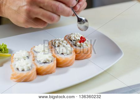 Hand holds spoon over sushi. Red caviar on sushi roll. Salmon caviar for uramaki rolls. Delicacy from japanese cuisine.