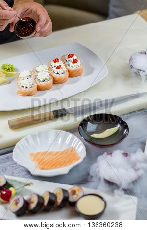 Sushi rolls lying on plate. Hand holds bowl with caviar. Fresh salmon caviar. Uramaki rolls cooked at cafe.