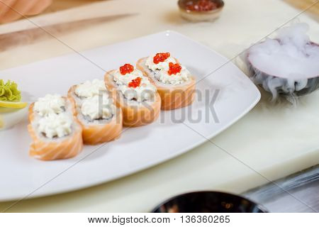 Sushi with caviar on plate. Cooking board with sushi plate. Uramaki rolls and dry ice. Sushi cafe at daytime.