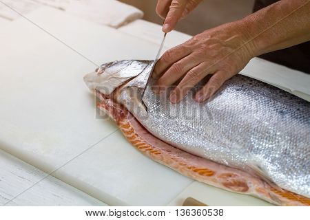 Knife cuts raw fish. Male hands with kitchen knife. Salmon bought in local shop. Product high in protein.