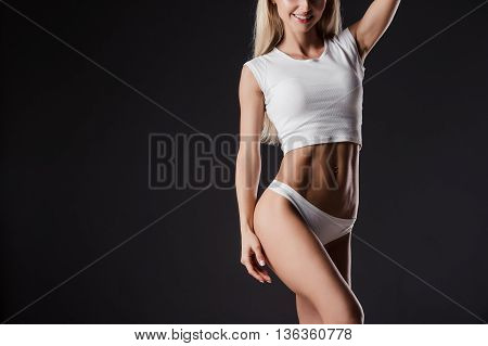 Female sexy blonde athlete woman in white lingerie with awesome shape figure showing perfect abdominal muscles over black studio background.