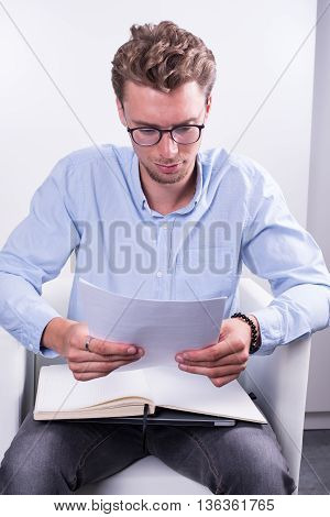 young man is reading a contract as preparation for a negotiation