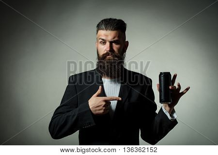 Handsome young man with long beard and moustache in black jacket holding tin beer can bottle in studio on grey background