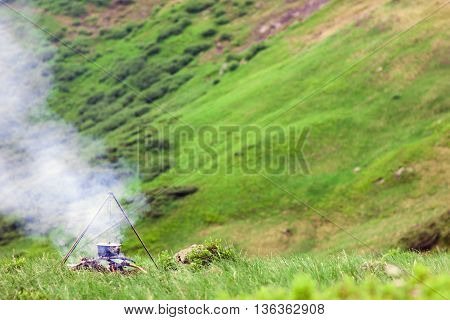 Camping fire and tourists bowler with preparing food in mountains