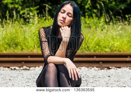 Young beautiful girl in black dress and nylons sitting on rail tracks and daydreaming, eyes closed, green grass and trees in background