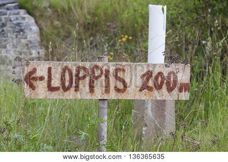 a wooden handwritten sign showing how far it to reach a yard sale