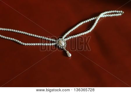 Elegant pearl necklace strands of precious white beads on brown silk background