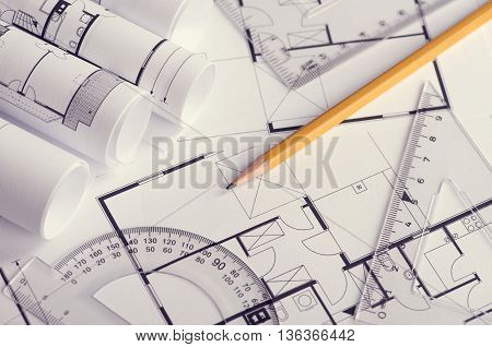 Toned and selective focus image.Several rolls of blueprints on an open blueprint