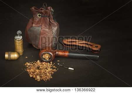 Old tobacco pipe and spilled tobacco, used on a black wooden background. Shabby old tobacco pipe. Wooden tobacco pipe on a black background. Relaxing with a tobacco pipe. Quiet place. Chain smoker.