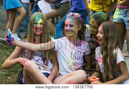 Lviv Ukraine - August 30 2015: Girls make self-portrait with mobile phone in a crowd of participants of the festival of color Lviv