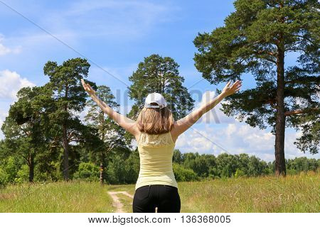 Young girl enjoys good weather and raises his hands to the sky.