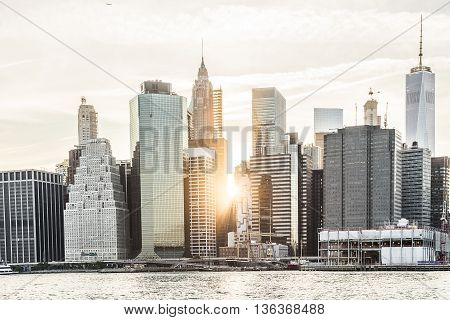 Sunburst between skyscrapers of the Manhattan skyline in New York City during sunset