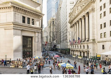 New York, USA - June 18, 2016: Wall street and the New York Stock exchange in New York City with hot dog stands
