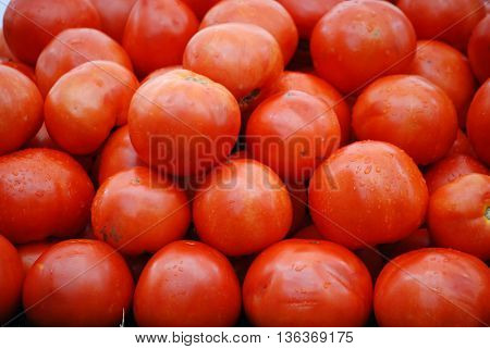 Collection of organic red tomatos at a farm stand.