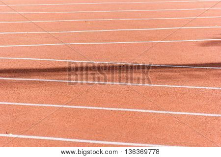 Red orange jogging in a stadium with markings