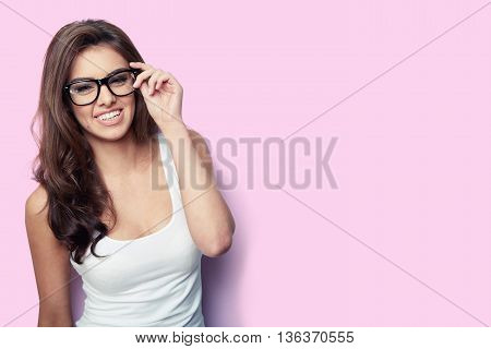 Smiling student girl in white shirt and glasses on pink background