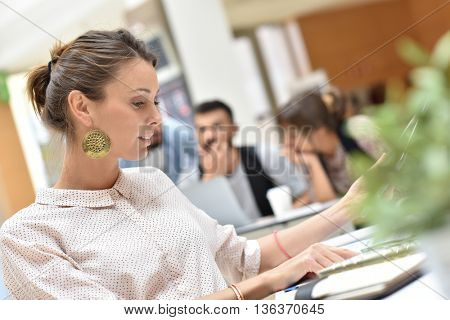 Attractive businesswoman in office working on tablet