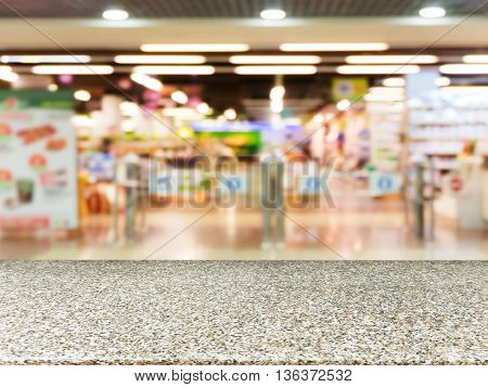 Marble board empty table in front of blurred background. Perspective marble over blur in entrance area of supermarket. Mock up for display or montage your product.