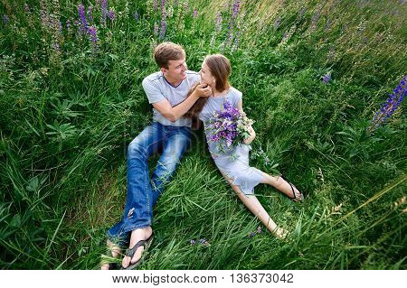 young happy beautiful couple sitting in green meadow.