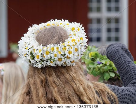 VADDO SWEDEN - JUNE 23 2016: Woman with oxeye daisy flowers in her hair during the traditional celebration of the Midsummer in Sweden June 23 2016