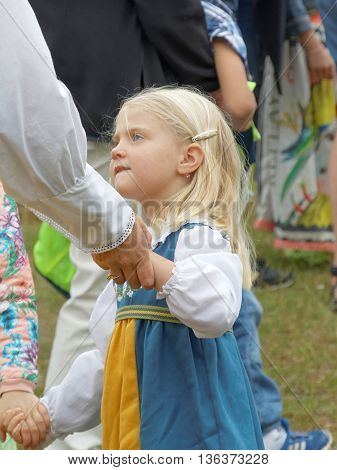 VADDO SWEDEN - JUNE 23 2016: Litte girl wearing traditional costume dancing around the the maypole celebrating the Midsummer in Sweden June 23 2016