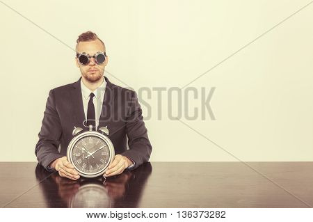 Businessman sitting at office desk with vintage goggles and clock