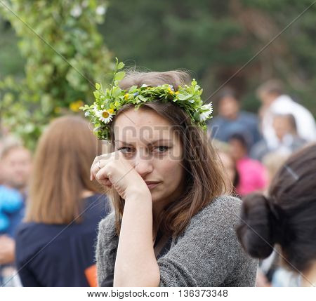 VADDO SWEDEN - JUNE 23 2016: Woman with flowers in her hair maypole in the background during the traditional dance celebrating the Midsommer in Sweden June 23 2016