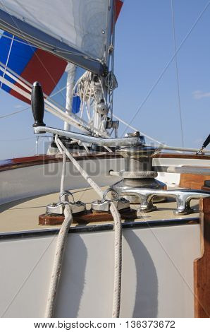 A detail of the rigging on a sailboat under sail. sailboat, rigging, detail, sails, wind, boat, deck, sky
