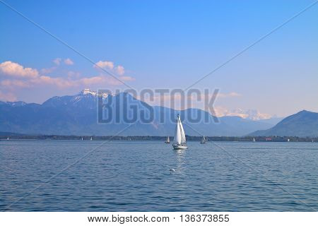 The photo was taken in Germany at Lake Chiemsee. The picture shows a walk on a yacht on mountain lake. In the background snowy mountains visible.