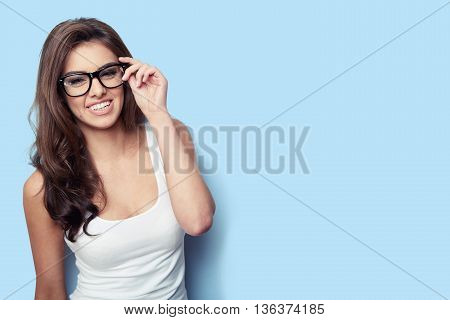 Smiling student girl in white shirt and glasses on blue background