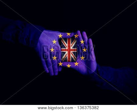 Close up of hands patterned with the flag of the European Community holding a card with the flag of the United Kingdom. Magician showing his trick with cards on black background
