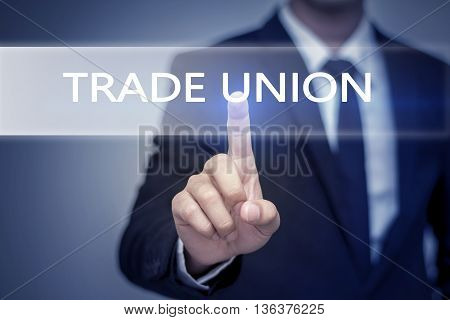 Businessman hand touching TRADE UNION button on virtual screen