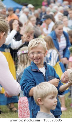 VADDO SWEDEN - JUNE 23 2016: Smiling young blonde boy dancing around the the maypole celebrating the Midsummer in Sweden June 23 2016