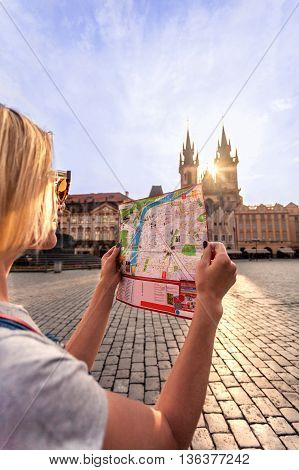 Young girl in Prague looks at the city map in the old town square. Travel guide, tourism in Europe, woman tourist with map on the street. Kostel Panny Marie pred Tynem. Church of the Virgin Mary.