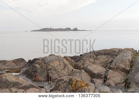 Gray rocks and the sea and a island in the background. No people