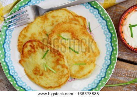 Potato fritters garnished with spring onions and bowl of sour cream on rustic wooden surface