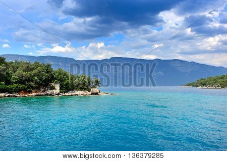 Beautiful seascape with island and the ruins of the old building. Aegean sea. Turkey