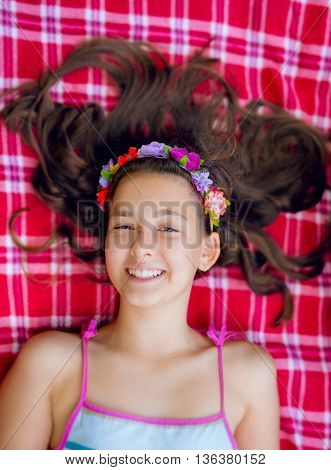 Smiling girl lying on her back on a blanket and relaxing