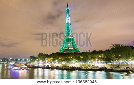 paris; France-June 27 2016 : The Eiffel tower lit up in green color for soccer Europe championship 2016 in France. The Eiffel tower is on of the most visited monuments in the wotrrld.