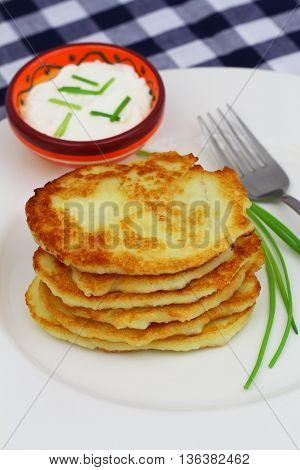 Potato fritters stacked up on white plate and bowl of sour cream