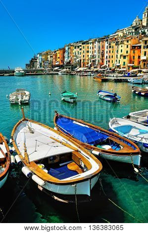 PortoVenere with colorful houses and fishing boats on blue water in Cinque Terre