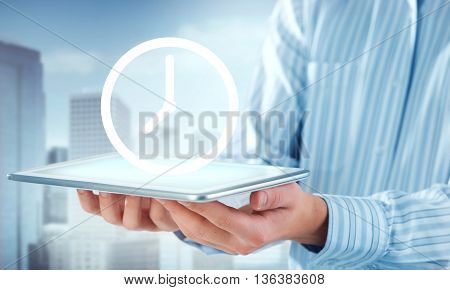 Hands of businessman holding tablet and clock icon on screen