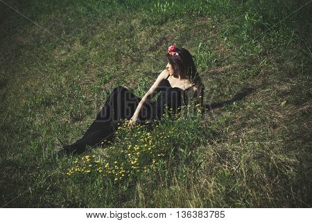 young woman in black dress and wreath of flowers lie on summer grass full body shot
