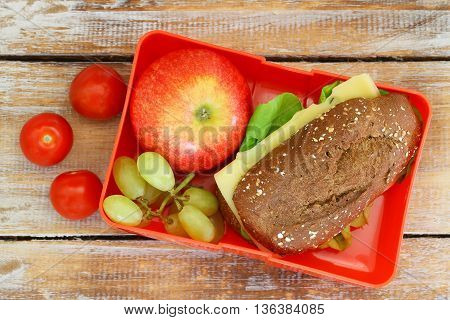 Healthy school lunch box containing whole grain roll with cheese and lettuce, cherry tomatoes, red apple and grapes