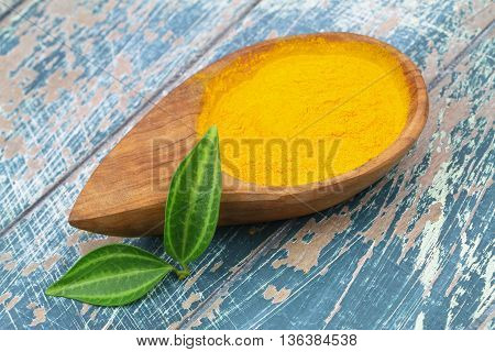 Tumeric powder in bamboo bowl on rustic wooden surface