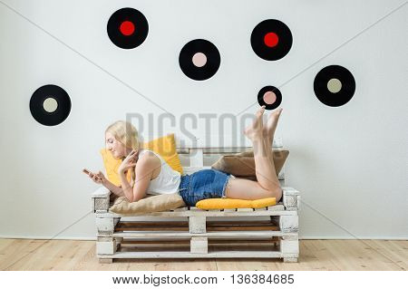 Beautiful Young Girl Listening To Music At Home Sitting On The Couch